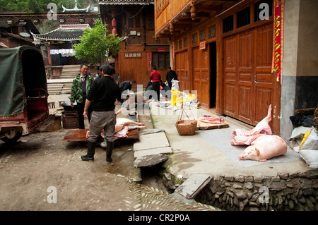 Slaughtering a pig in front of a traditional Dong wooden house, Zhaoxing Dong Village, Southern China - Stock Photo