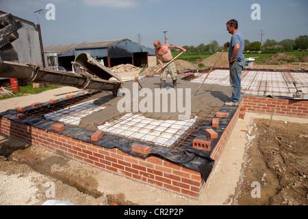 Pouring Readymix concrete into passive slab foundation Colemans Hill Farm Ecobuild Mickleton UK - Stock Photo