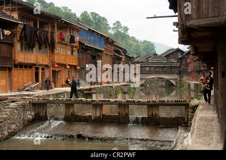 A small bridge crossing a stream and a 'Wind and Rain' bridge, Zhaoxing Dong Village, Southern China - Stock Photo