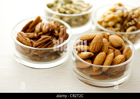 Assortment of nuts in glass containers - Stock Photo