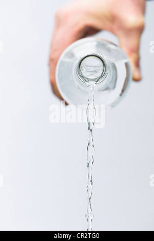 Hand pouring mineral water from a glass bottle against white background - Stock Photo