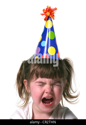Child Throwing a Tantrum Wearing a Birthday Hat - Stock Photo