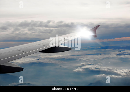 Right wing, Airbus A 319 in flight above clouds - Stock Photo