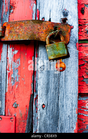 Old door locked with a padlock with a rusty key still sticking in it - Stock Photo