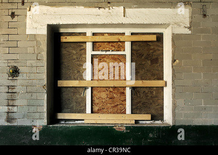 Boarded up old window in a derelict building - Stock Photo