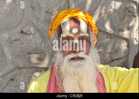 Sadhu holy man with brightly painted face and beard, portrait, Hinduism, Makhan Tole square in front of the Krishna - Stock Photo