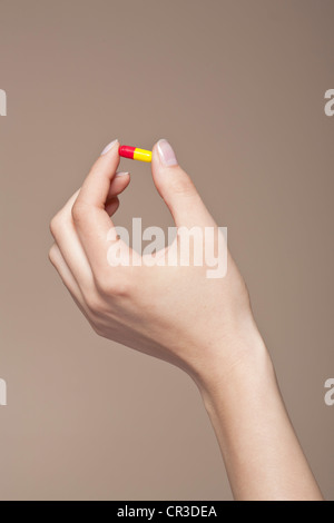Hand of a young woman holding a pill, capsule between her fingers - Stock Photo