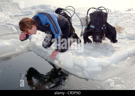 Diver, preparing for subglacial diving, ice diving, in the frozen Black Sea, a rare phenomenon, last time it occured - Stock Photo