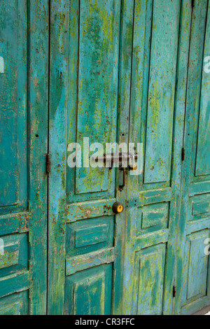 Distressed paintwork on bolted wooden door - Stock Photo