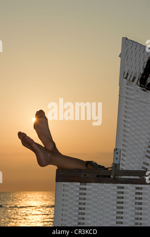 Roofed wicker beach chair and bare feet at sunset, Westerland, Sylt island, Schleswig-Holstein, Germany, Europe - Stock Photo
