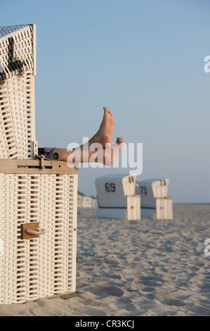 Roofed wicker beach chair and bare feet, Westerland, Sylt island, Schleswig-Holstein, Germany, Europe - Stock Photo