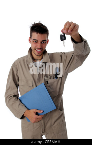 Friendly mechanic clutching the job card and holding up car keys to show he has completed the repair or service - Stock Photo
