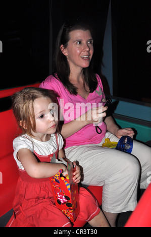 Mother and Daughter enjoy the ride through the attraction 'It's a Small World' at Disneyland, Anaheim, California - Stock Photo