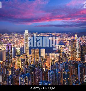 Hong Kong skyline illuminated at twilight, square format. - Stock Photo