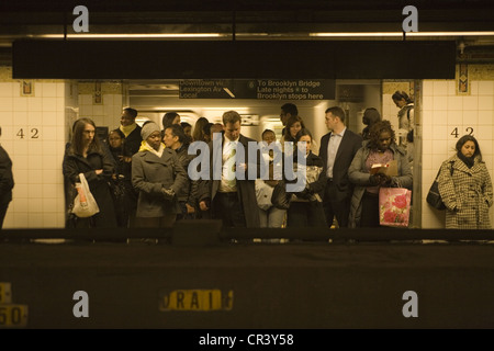 Commuters wait on the platform for a downtown subway train at Grand Central Station in NYC - Stock Photo