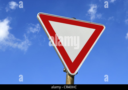 Traffic sign, give way, against a blue sky with clouds - Stock Photo