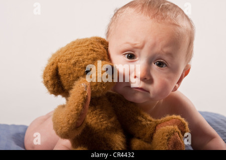 Baby boy, 8 months, with a teddy bear - Stock Photo