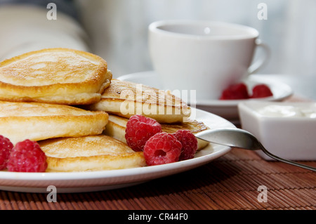 Sweet pancakes with raspberries, sour cream and cup of tea - Stock Photo