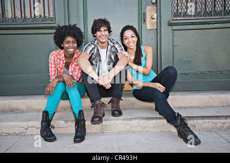 Friends hanging out on front stoop - Stock Photo
