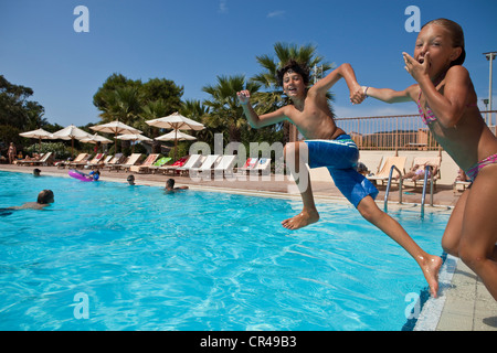 France, Corse du Sud, children jumping into the swimming pool - Stock Photo