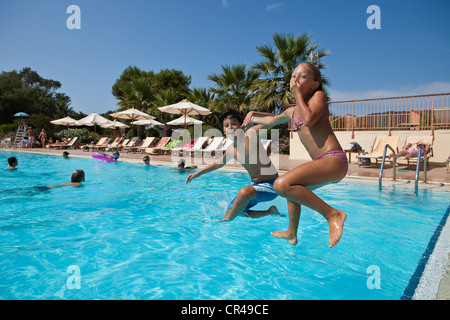 France, Corse-du-Sud, children jumping into the swimming pool - Stock Photo