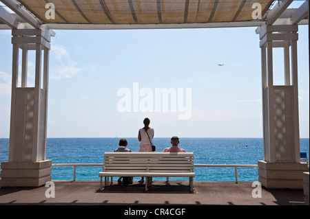 France, Alpes Maritimes, Nice, Promenade des Anglais, walkers sat on a bench and watching the sea - Stock Photo
