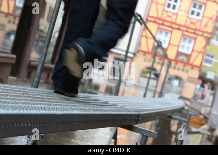 Man walking along a temporary raised footway, flood on 17/01/2011 in Wertheim, looking over the street of Eichelgasse - Stock Photo