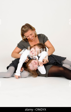 Young girls with her mother, cuddling and having fun, motherly love - Stock Photo