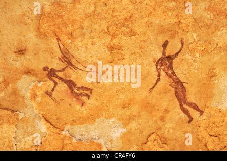 Painted warriors or hunters, neolithic rock art at Tin Meskis, Adrar n'Ahnet, Algeria, Sahara, North Africa - Stock Photo
