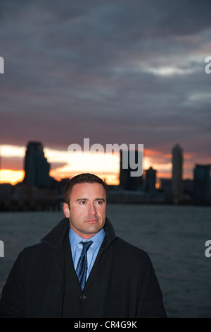 Portrait of caucasian man in business suit with coat on streets of New York City America during sun set - Stock Photo