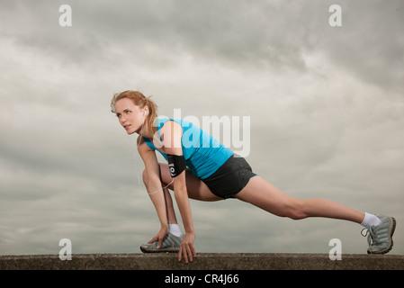 woman starting running listening to her ipod - Stock Photo