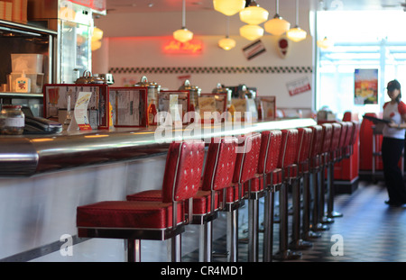 A shot of an empty breakfast bar in a diner with a row of empty bar stools and an out of focus waitress at the edge - Stock Photo