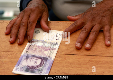 an old lady's hands either side of a small bundle of £20 notes - Stock Photo