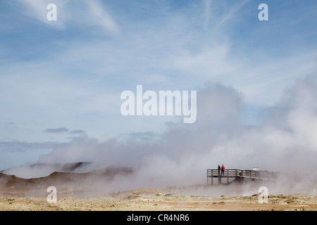 Tourists watch geothermal steam rising from the ground at Svartsengi Power Station, Reykjanes, Iceland - Stock Photo