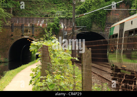 a bridge crossing a railway and a canal and a train approaching one of the bridge arches - Stock Photo