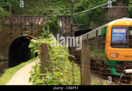 a bridge crossing a railway and a canal and a train entering one of the bridge arches - Stock Photo