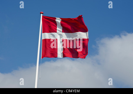 Danish national flag against a blue sky with clouds, Saeby, North Jutland region, Denmark, Europe - Stock Photo