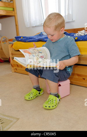 Boy, 3 years, leafing through a book in the children's room - Stock Photo