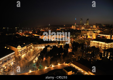 Historic city centre of Baku, dusk, UNESCO World Heritage Site, with the high-rise towers of the three Flame Towers - Stock Photo
