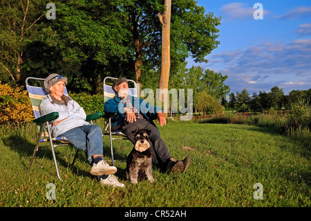 Couple with a miniature schnauzer at a camping site, Villars-les-Dombes, Rhone-Alpes, Ain, France, Europe - Stock Photo