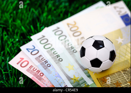 Football on euro notes, symbolic image for a betting scandal - Stock Photo