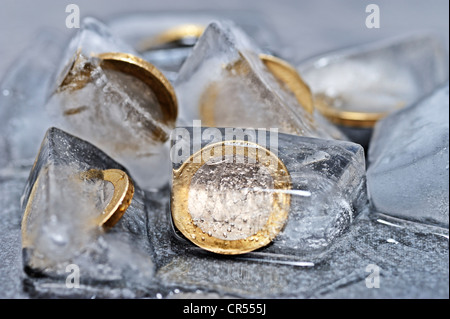 One-euro coins in ice cubes, symbolic image for frozen funds - Stock Photo
