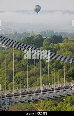 A hot air balloon ascends above early morning mist behind Brunel's landmark Clifton suspension bridge Bristol UK - Stock Photo