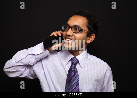 A happy business man talking over a mobile phone. - Stock Photo