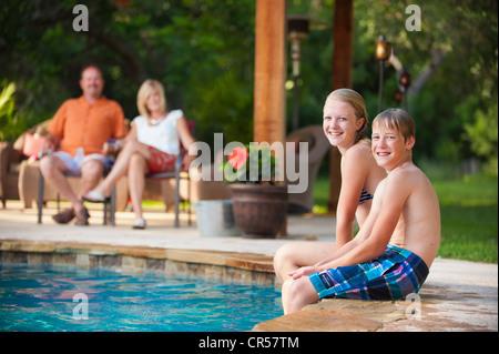 Family fun at the backyard swimming pool - Stock Photo