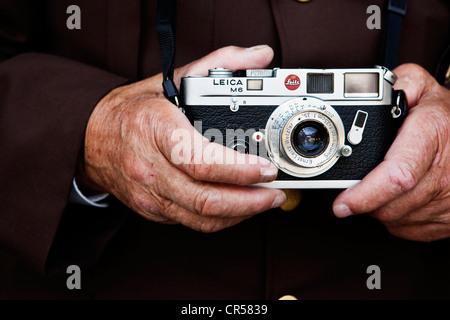 Hands of an elderly man holding a Leica rangefinder camera, North Tyrol, Austria, Europe - Stock Photo
