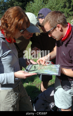 Group of hikers navigating using map and compass, Nizke Tatry National Park, Slovakia - Stock Photo