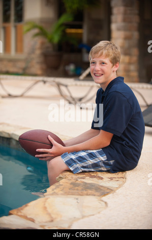 Young boy with american football - Stock Photo