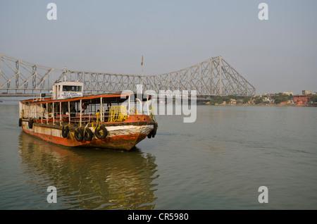 Ferry boat connecting Kolkata and Howrah, in front of the 705 m long Howrah Bridge, Kolkata, West Bengal, India, - Stock Photo