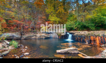 Small waterfall in a broken dam surrounded by early fall foliage. - Stock Photo